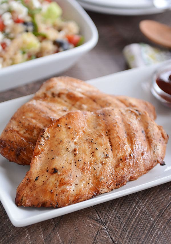 Two grilled chicken breast on a white platter.