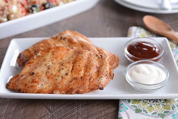 Two grilled chicken breasts next to two small glass cups of dipping sauce on a white platter.