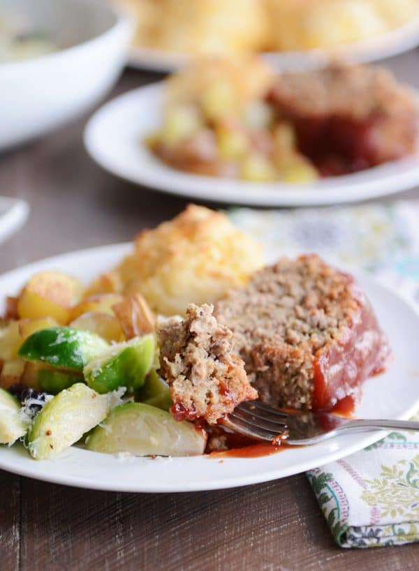 A slice of the best glazed meatloaf on a plate with vegetables and a biscuit.