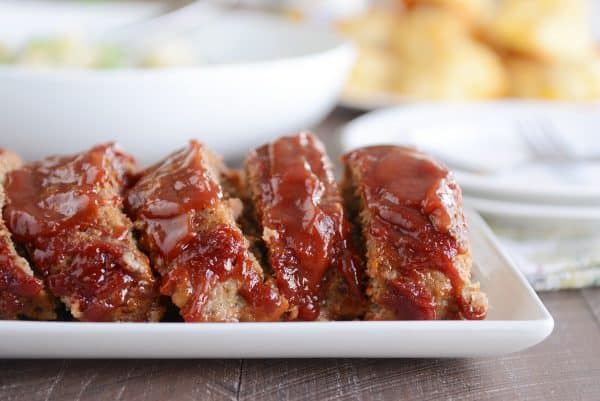 Slices of the best glazed meatloaf on white platter.