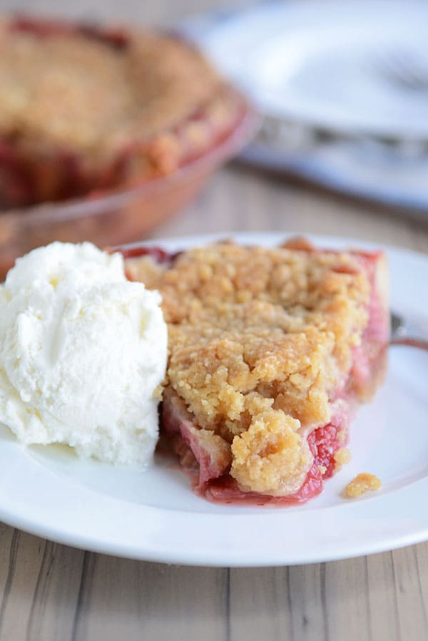 A streusel-topped, berry-filled slice of pie on a white plate, with a scoop of vanilla ice cream next to it, and the rest of the pie in a pie plate in the background.