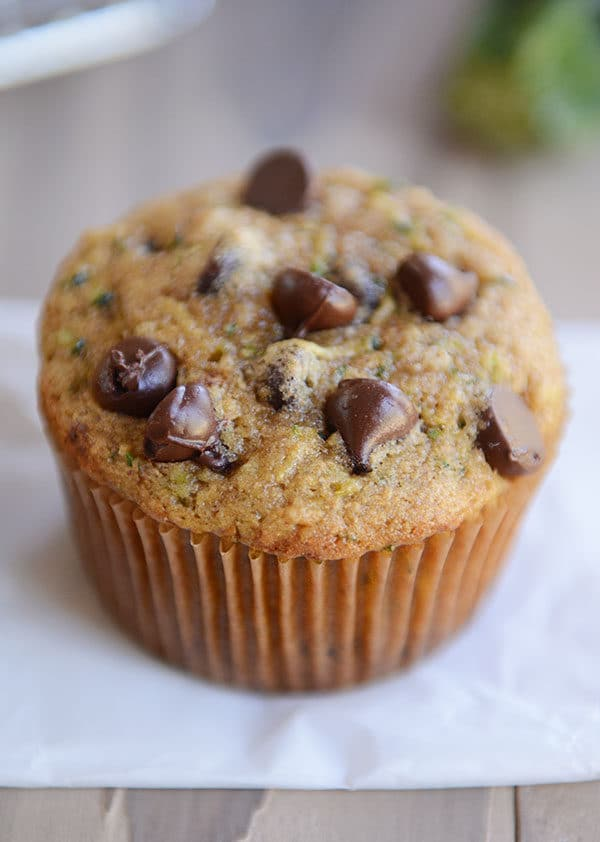 Top view of a chocolate chip topped zucchini muffin on a piece of parchment paper.