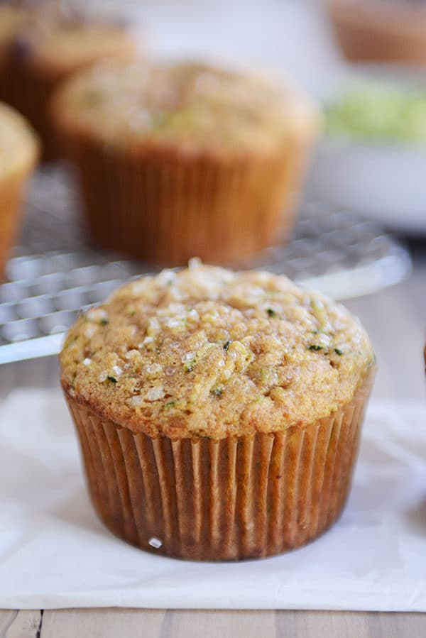A zucchini muffin on a piece of parchment with other muffins in the background on a cooling rack.