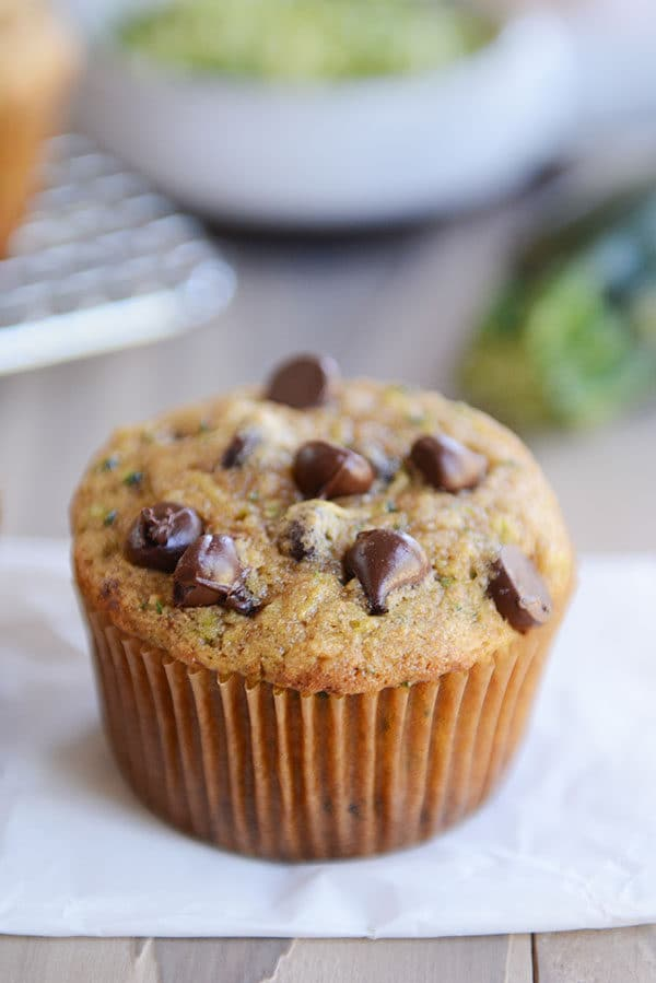 A chocolate chip topped zucchini muffin on a piece of parchment paper.