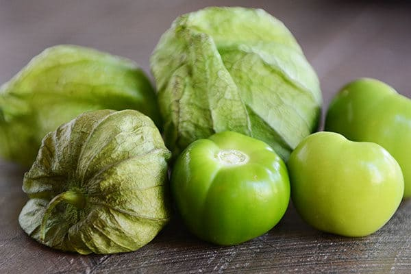 Green tomatillos on a counter.