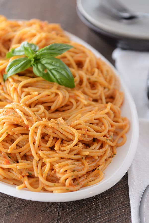 A large oval white bowl full of cooked tomato pesto pasta.