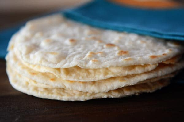 A stack of homemade cooked tortillas under a blue napkin.