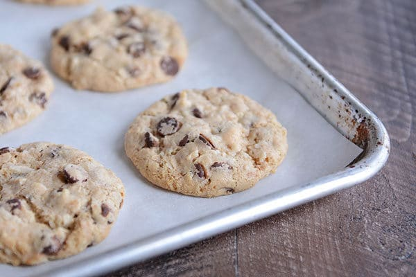Chocolate chip cookies on a parchment-lined cookie sheet.
