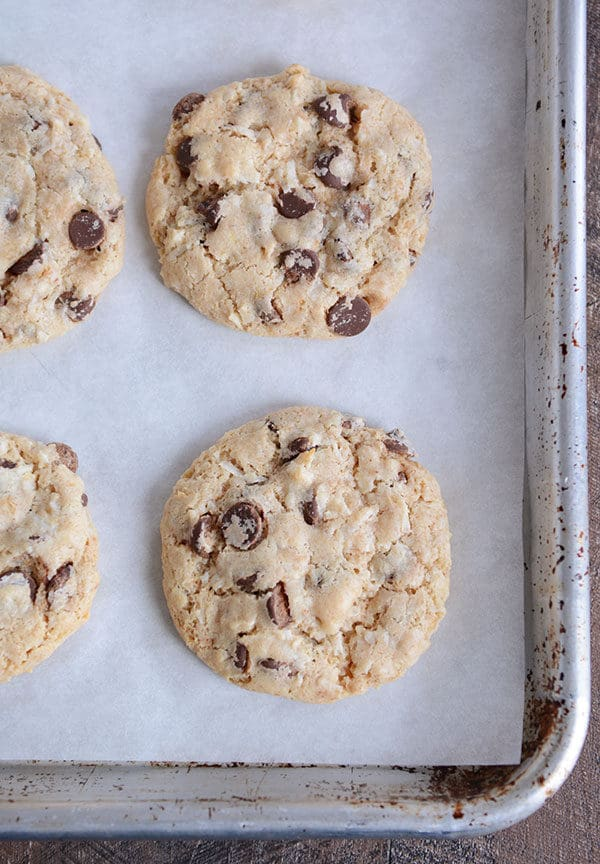 Top view of cooked chocolate chip cookies on a parchment-lined cookie sheet.