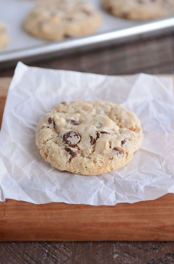 A chocolate chip cookie on a square of parchment paper.