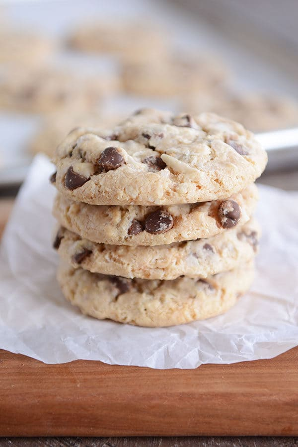 Four chocolate chip cookies stacked on top of each other on a piece of parchment paper.