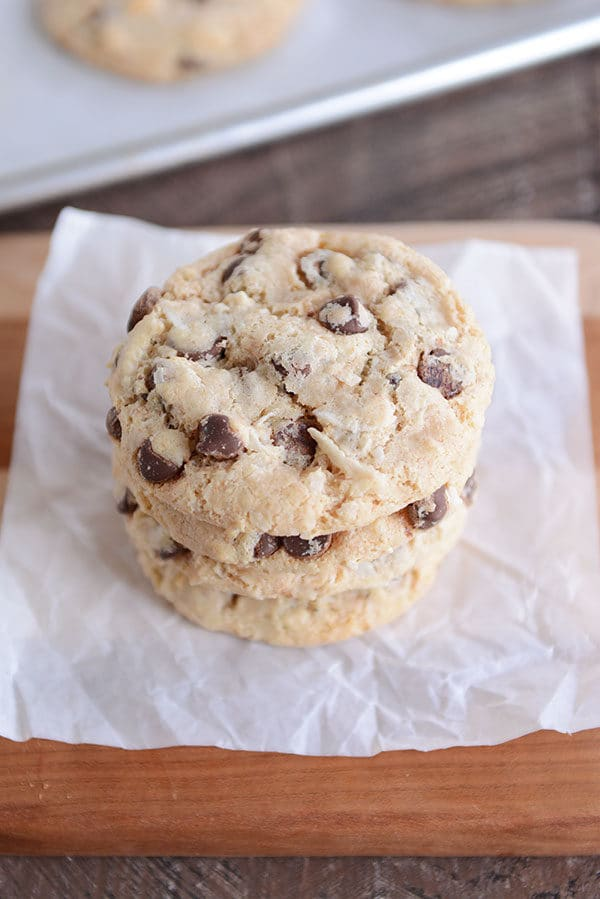 Three chocolate chip cookies stacked on top of each other on a piece of parchment.