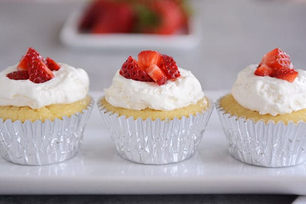 Three tres leches cupcakes in silver muffin liners lined up on a white platter.