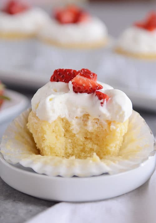 A tres leches cupcake topped with frosting and strawberries with a bite taken out.