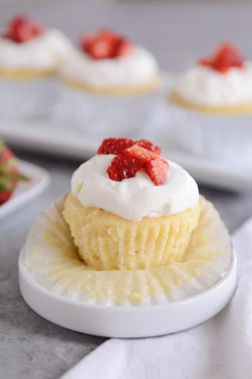 A tres leches cupcakes topped with frosting and chopped strawberries on a white muffin liner.