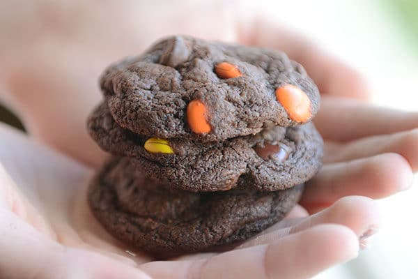 A hand holding three chocolate M&M cookies stacked on top of each other.
