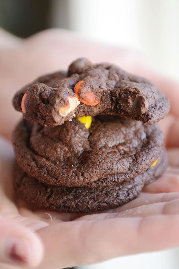 A hand holding a stack of chocolate M&M cookies with a a bite taken out of the top one.