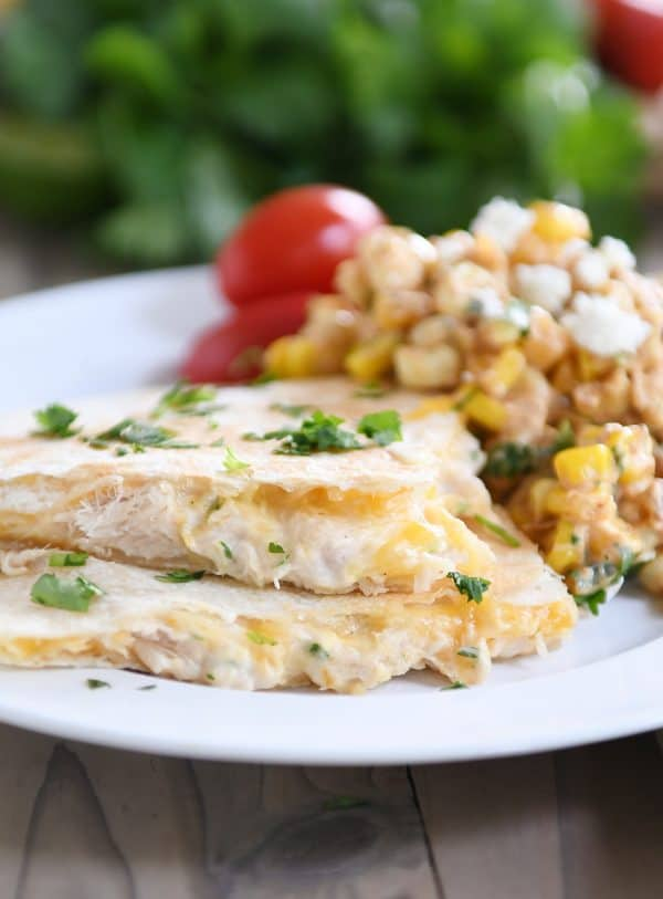 Stack of two triangles of tuna quesadilla melts on white plate with corn salad.