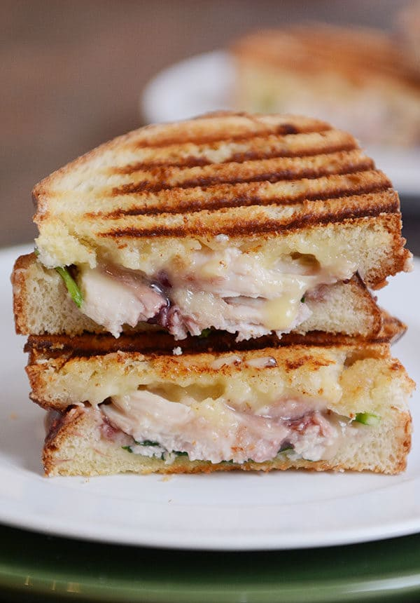 A turkey panini with cranberry and melted brie cut in half on a white plate.