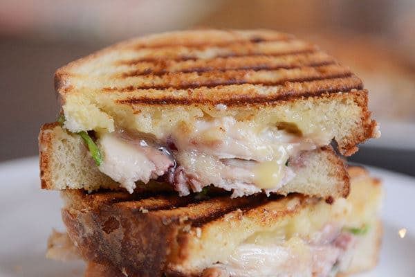 A turkey brie panini cut in half and stacked on a white plate.