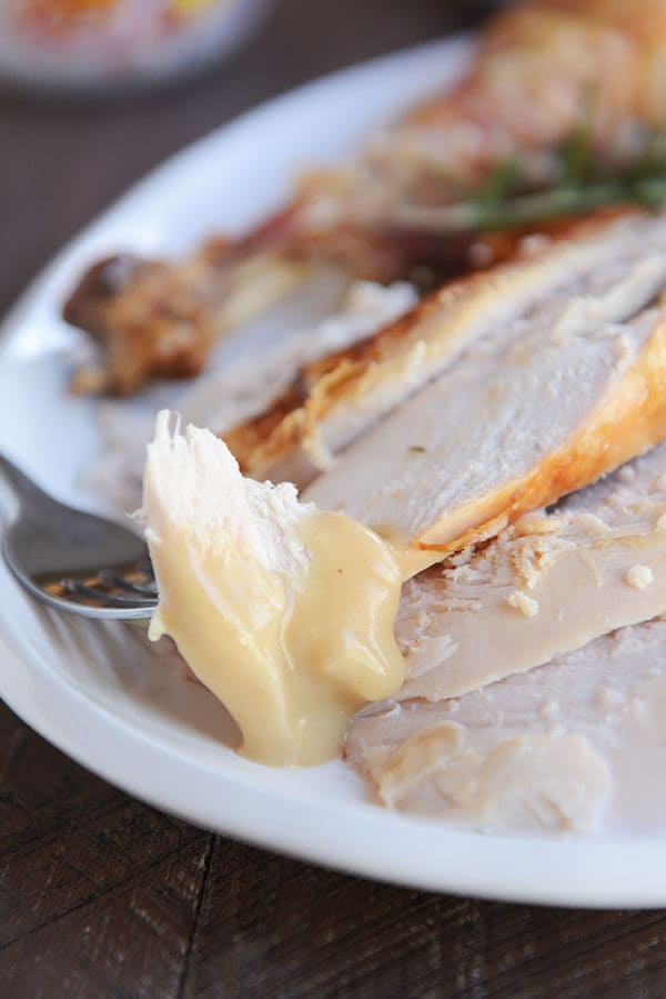 A fork taking a bite of turkey off of a platter of turkey slices.