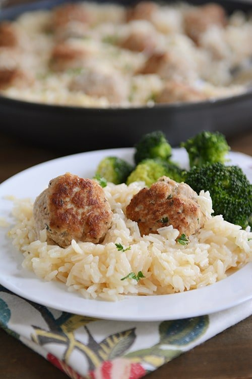 A plate of rice and meatballs with a side of broccoli.