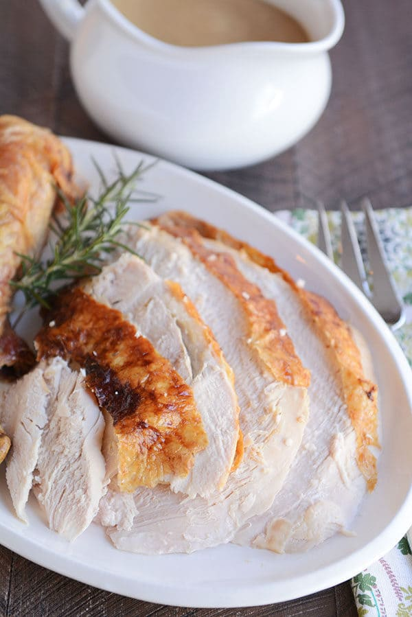 Thick turkey slices cut up on a white oval platter.