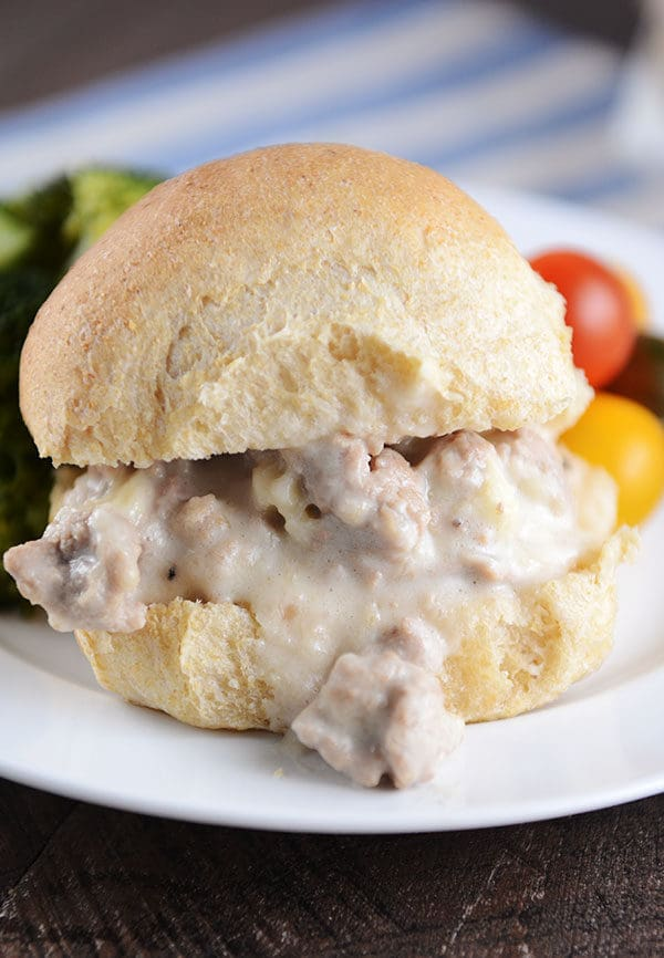 A creamy turkey swiss sloppy joe on a whole wheat roll on a white plate with fresh veggies next to it.