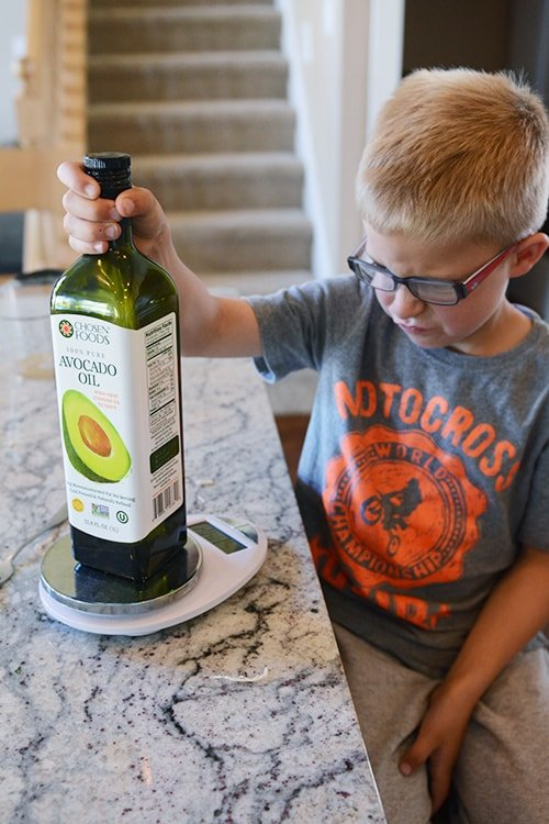 A little boy looking at a jar of avocado oil.