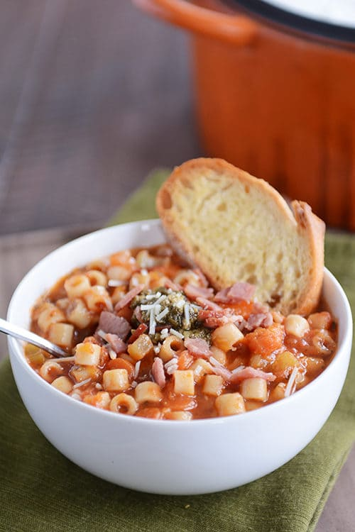 A white bowl full of winter minestrone soup with a piece of garlic bread on the side.