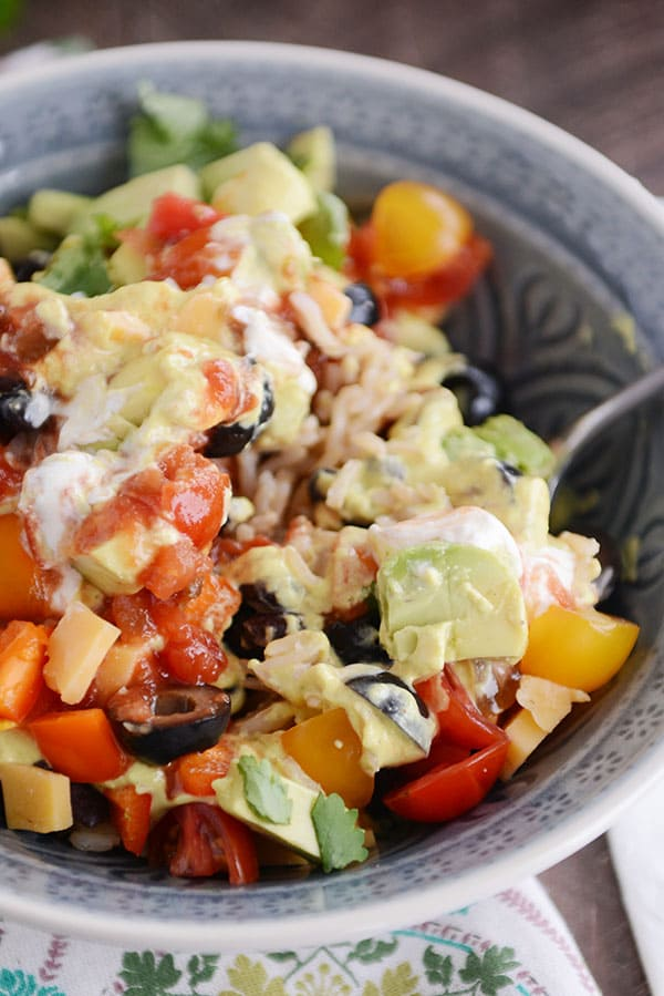 A bowl full of rice, topped with cubes of cheese, sliced olives, chopped avocado, tomatoes, and salsa.