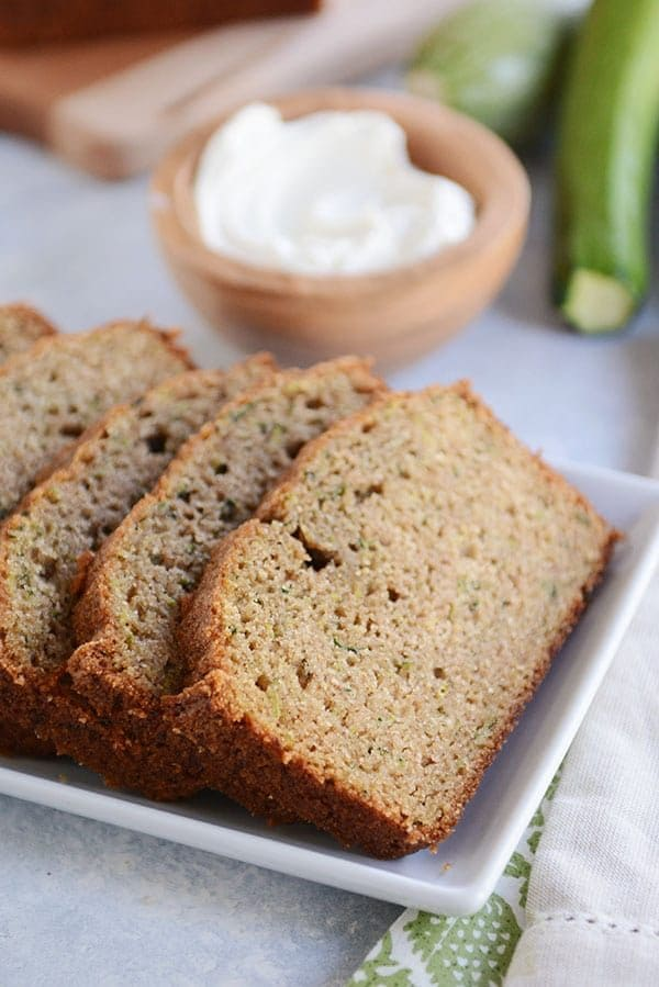 Slices of zucchini bread on a white platter with a wooden bowl of butter behind it.