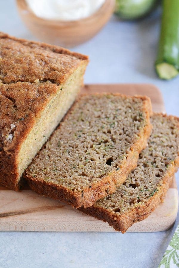 A loaf of zucchini bread with two slices cut off on a wooden cutting board.