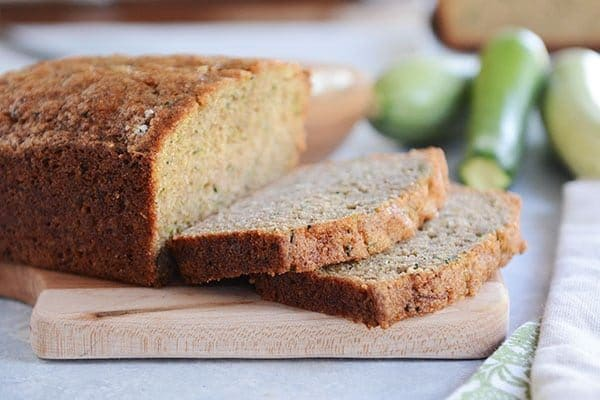 A loaf of zucchini bread with two slices cut off and fresh zucchini in the background.