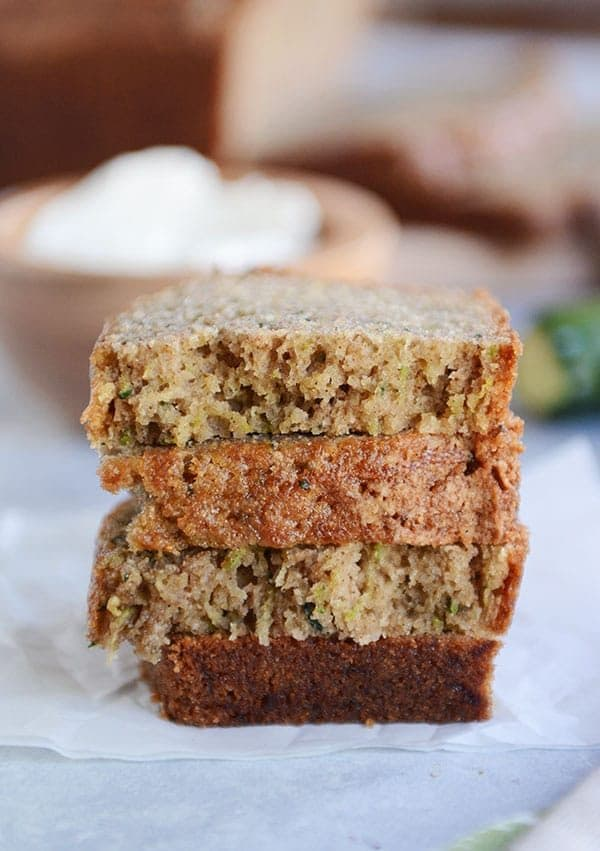Four half pieces of zucchini bread stacked on top of each on a piece of parchment.