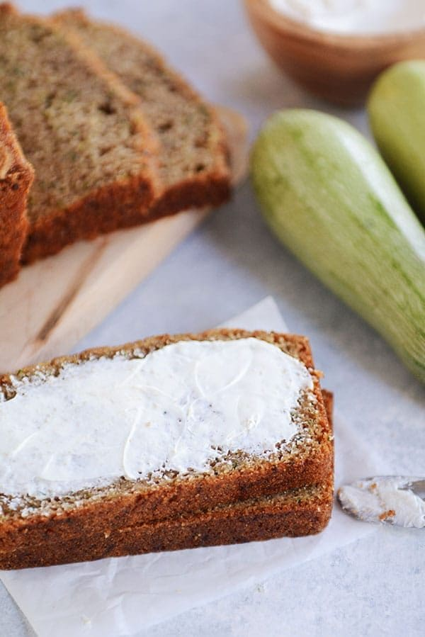 Two slices of zucchini bread stacked on top of each with butter smeared over the top piece.